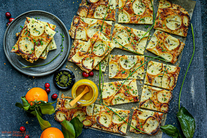 A serving of Honey Mustard Potato Tart on a small round plate next to the sliced tart with leaves and oranges around,