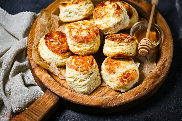 The best flaky biscuits on a round wooden board with honey.