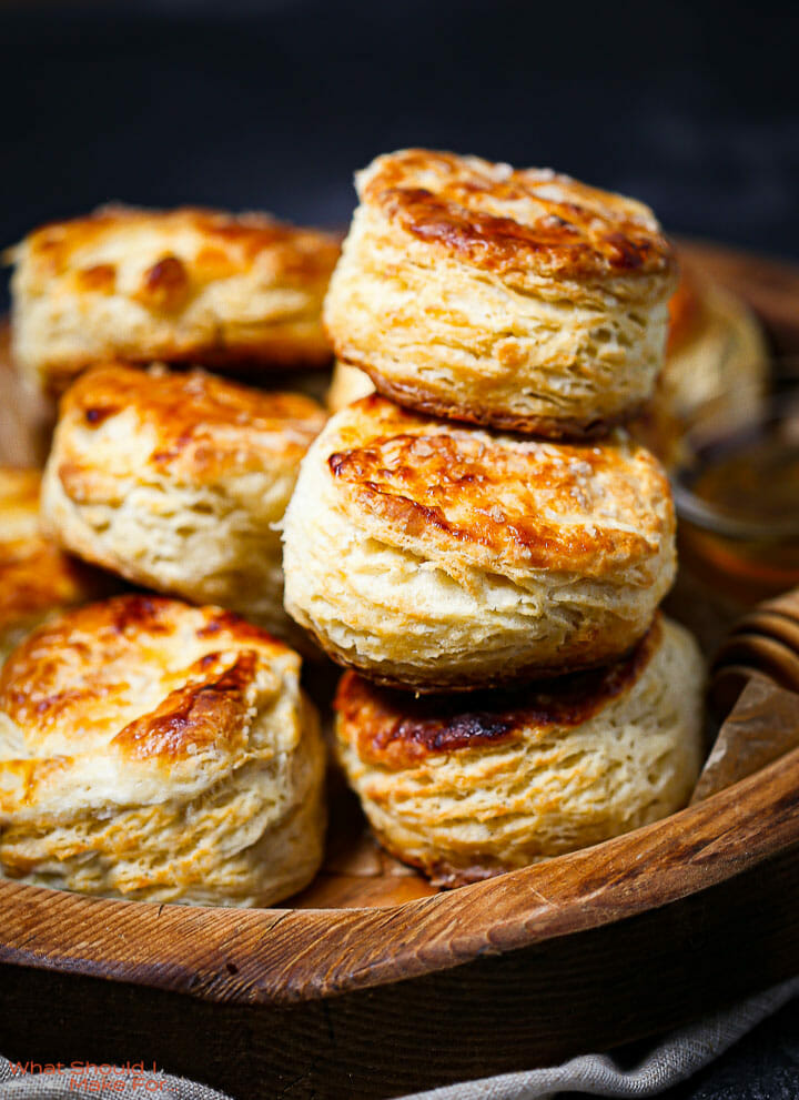 The best flaky biscuits stacked up on a wooden serving board.