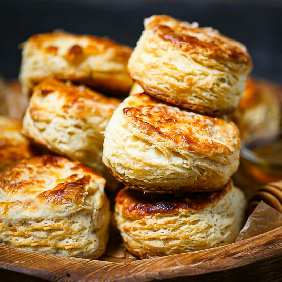 Close up of the best flaky biscuits stacked up on a wooden board.
