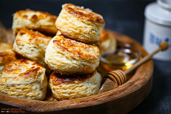 Close up of the best flaky biscuits with honey and butter in the background.