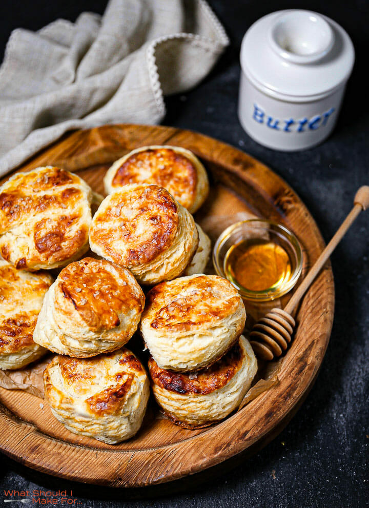 The best flaky biscuits on a round wooden serving tray with honey and butter.