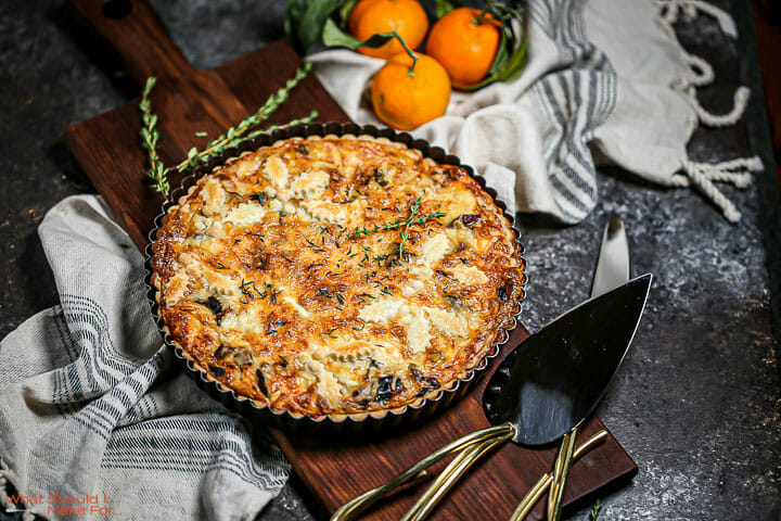A savory mushroom tart on a wood board with clementines, fresh thyme and serving utensils next to it.