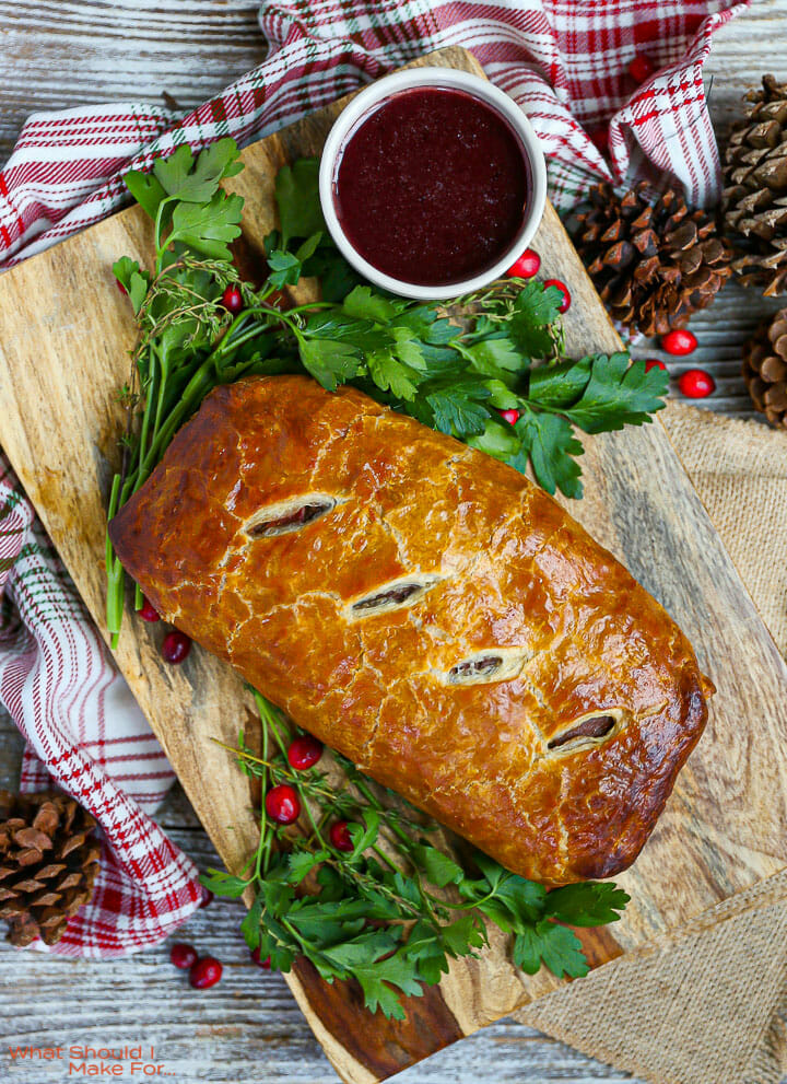 An unsliced Beef Wellington with Red Wine Sauce on a wood board with parsley and cranberries scattered around.
