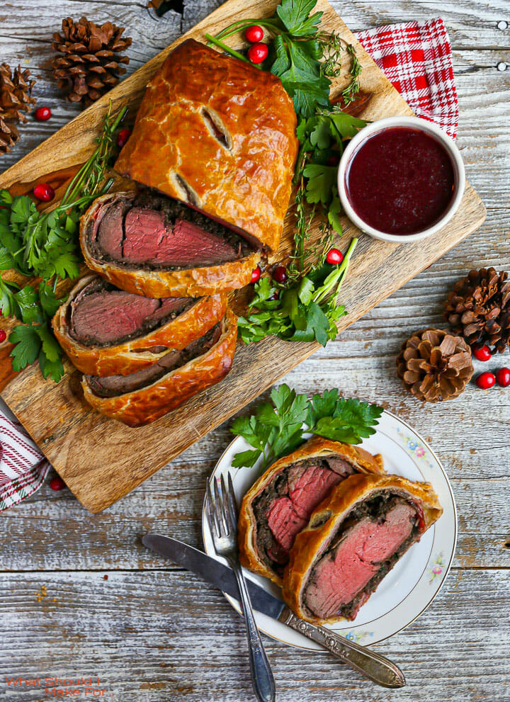 A sliced Beef Wellington with Red Wine Sauce on a cutting board with two slices on a small white plate.