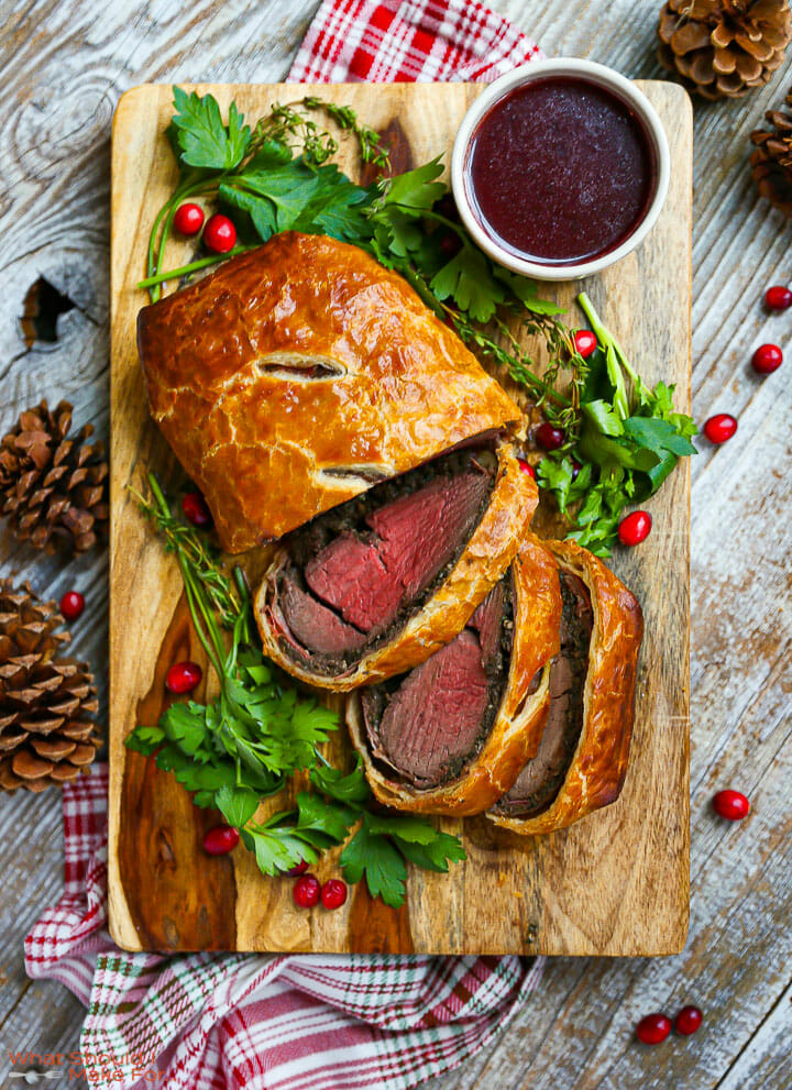 Overhead shot of Beef Wellington with Red Wine Sauce sliced on a cutting board with parsley scattered around.