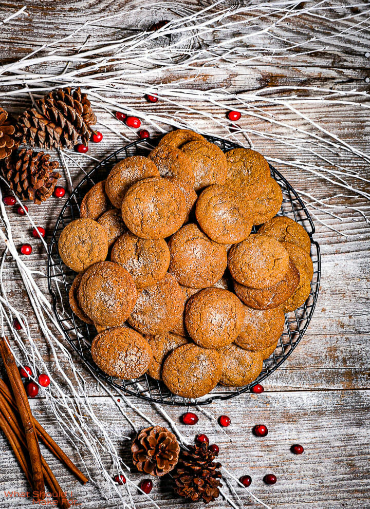Soft Molasses Cookies on a round wire rack with white branches and pine cones around.