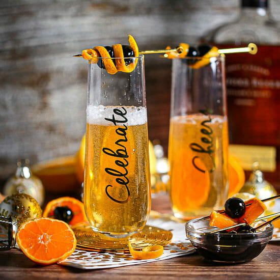 """Two Bourbon Champagne Cocktails in tall flute glasses inscribed with """"Celebrate"""" garnished with cherries and a twist of orange."""