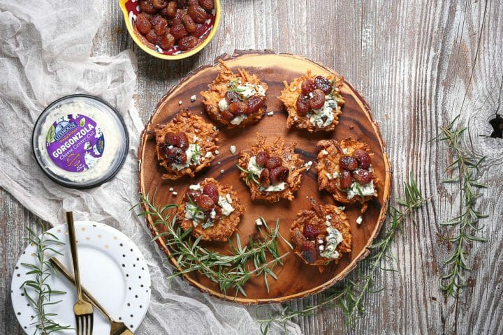 Potato Latkes with Gorgonzola and Roasted Red Grapes on a white-washed wood table with gorgonzola and grapes in small dishes for serving.