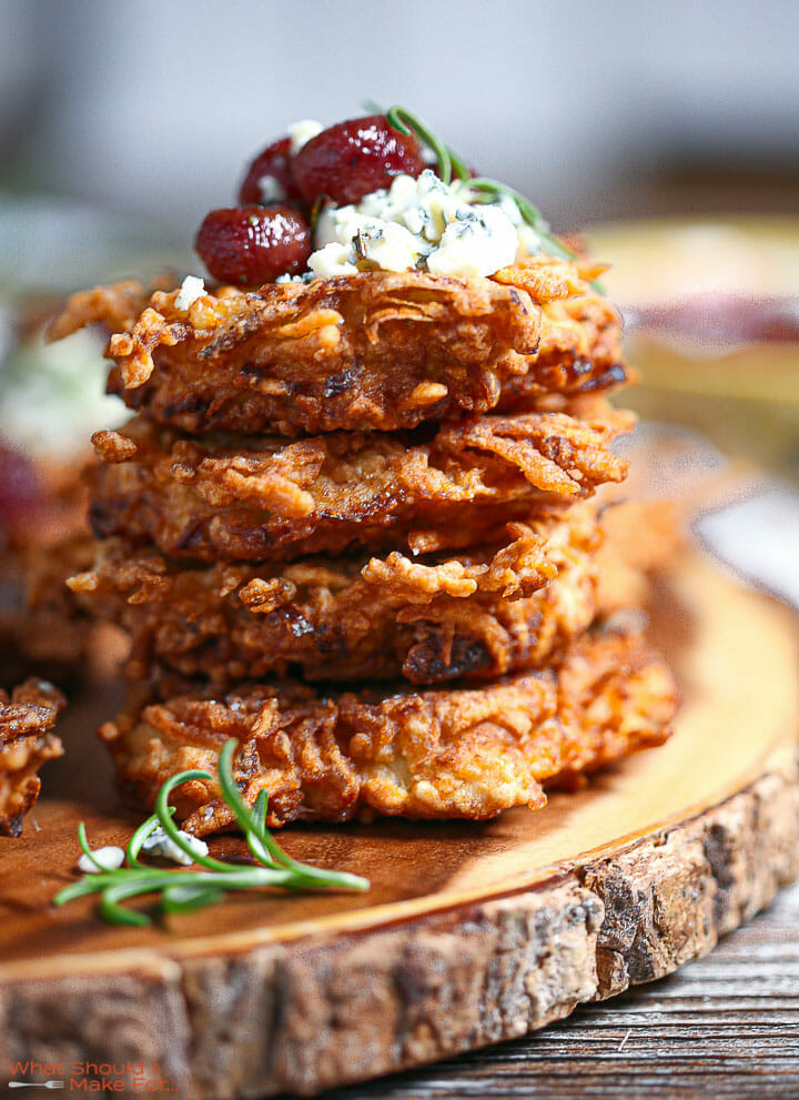 A stack of Potato Latkes with Gorgonzola and Roasted Red Grapes on a wood board.