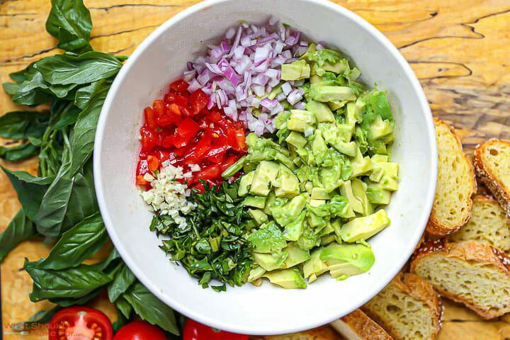 The ingredients for Italian guacamole prepped and in a bowl with basil scattered around.