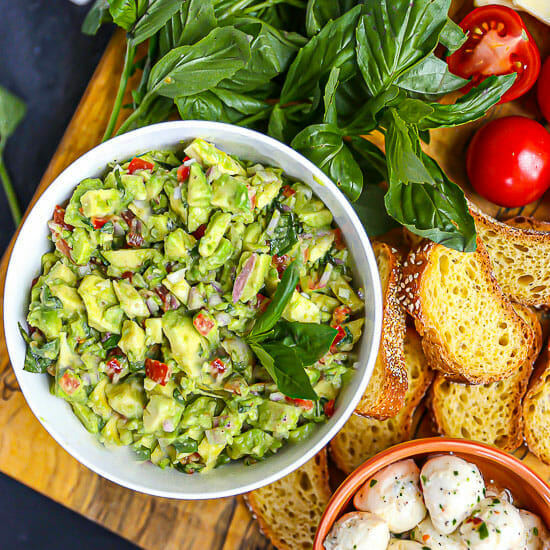 Overhead shot of Italian guacamole in a bowl with bread and basil scattered around.