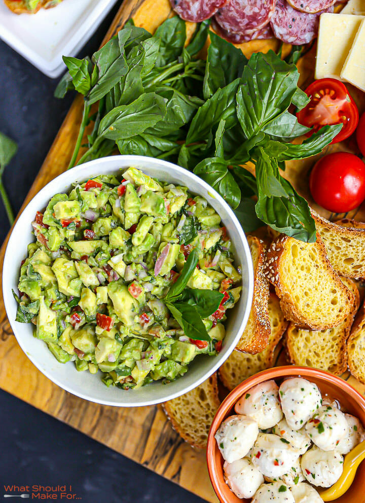 Italian guacamole in a white bowl on a board with bread, basil and mozzarella on the board.