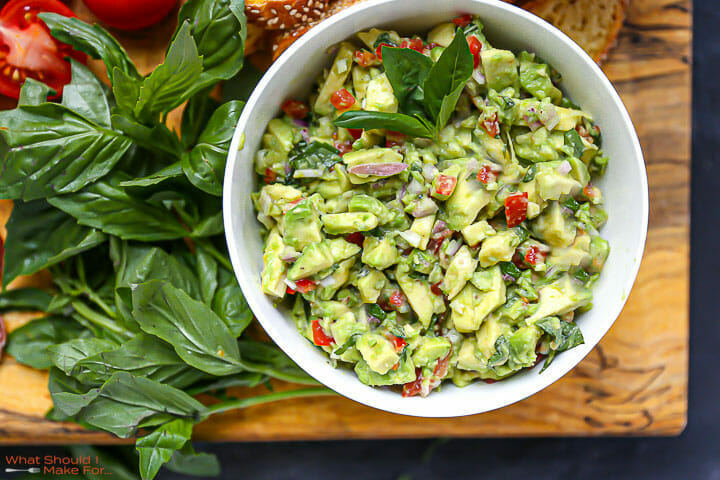 Italian guacamole in a white bowl on a wood board with basil scattered around.