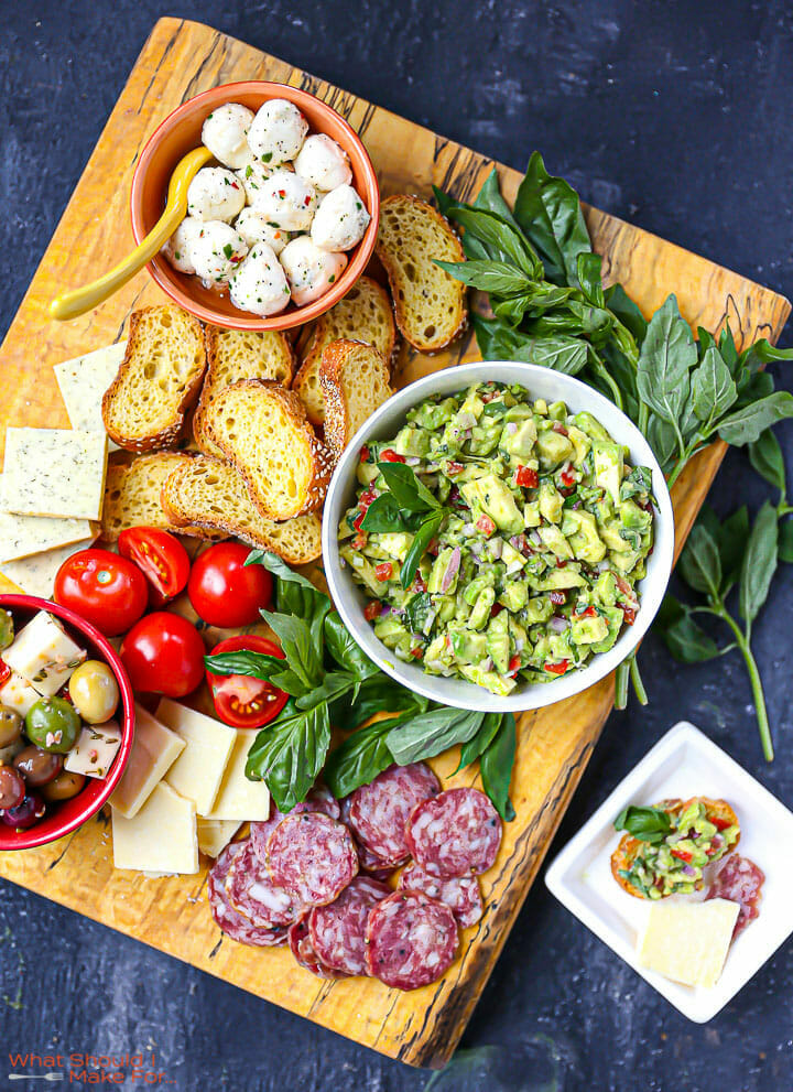 Italian Guacamole on a large wood board with bread, cheese, olives, basil, and salami and a serving on a small white plate.