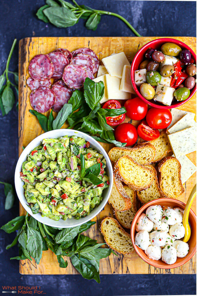Italian Guacamole on a large wood board with bread, cheese, olives and salami.