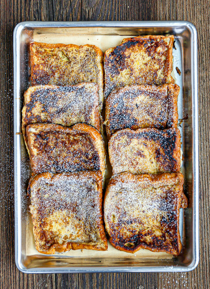 Brioche French Toast on a sheet tray sprinkled with powdered sugar.