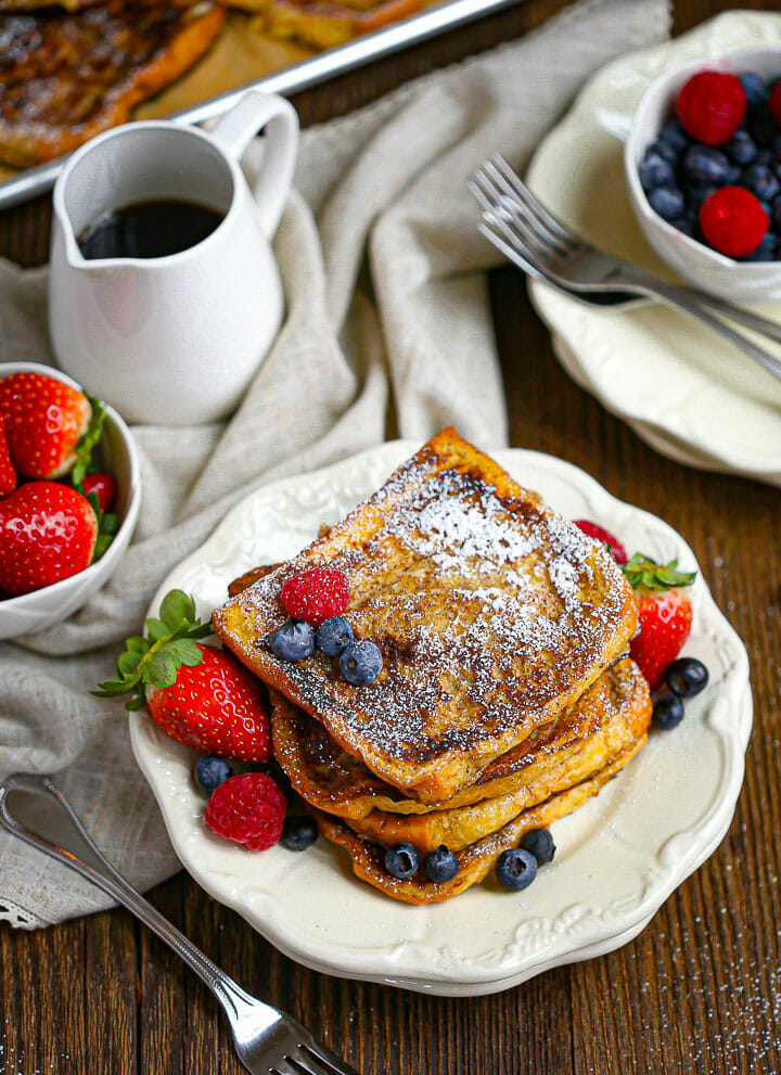 A serving of Brioche French Toast on a plate with berries and syrup in a pitcher.