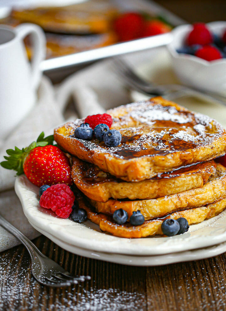A serving of Brioche French Toast on a plate drizzled with syrup and served with berries.