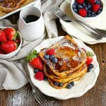 Brioche French Toast on a plate sprinkled with powdered sugar,drizzlwd with syrup and served with berries.