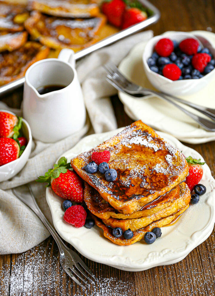 Brioche French Toast on a plate with a pitcher or syrup and sprinkled with berries.