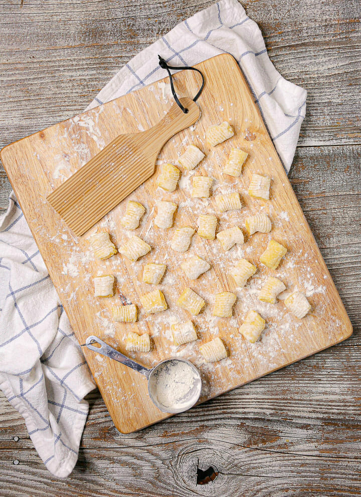 Overhead shot of homemade gnocchi on a wood board with a measuring cup and a ridged paddle.