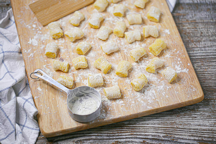 Potato gnocchi on a wood board with a measuring cup with flour.