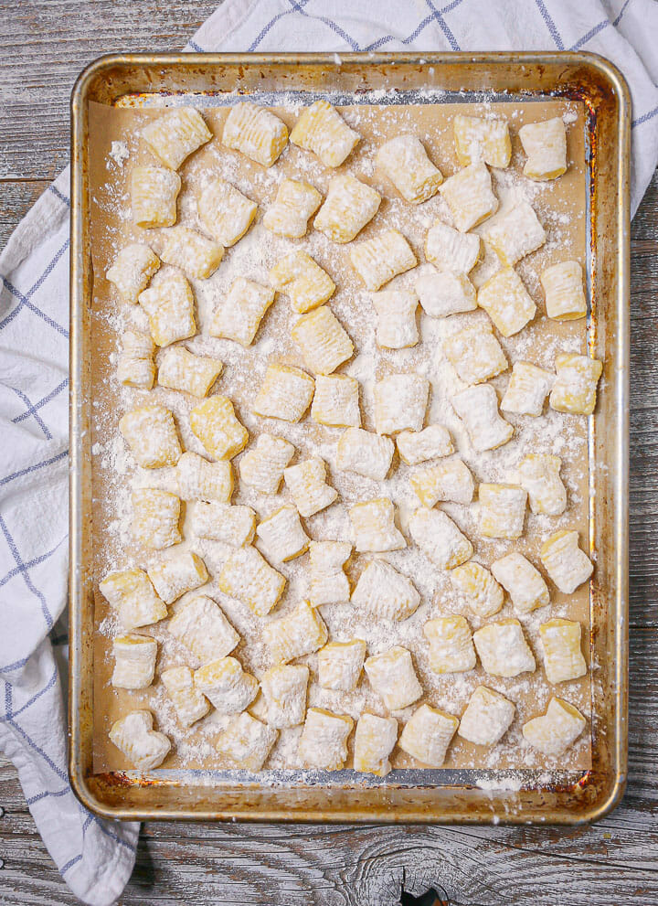 Overhead shot of potato gnocchi on a sheet pan with a kitchen towel underneath.