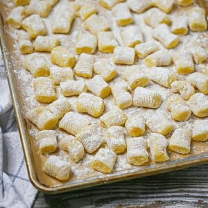 Homemade potato gnocchi floured and uncooked on a sheet pan.
