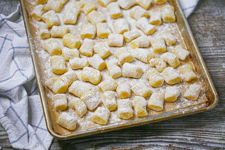 Close up of homemade potato gnocchi floured and uncooked on a sheet pan.