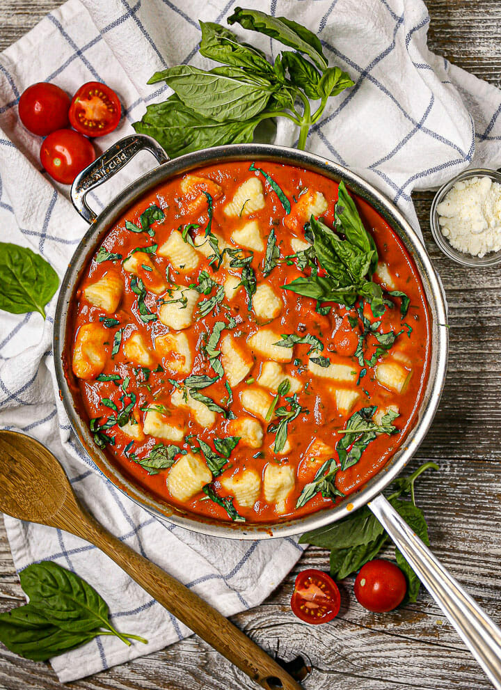 Overhead shot of Gnocchi in Creamy Tomato Basil Sauce in a saucepan on a white and blue linen.