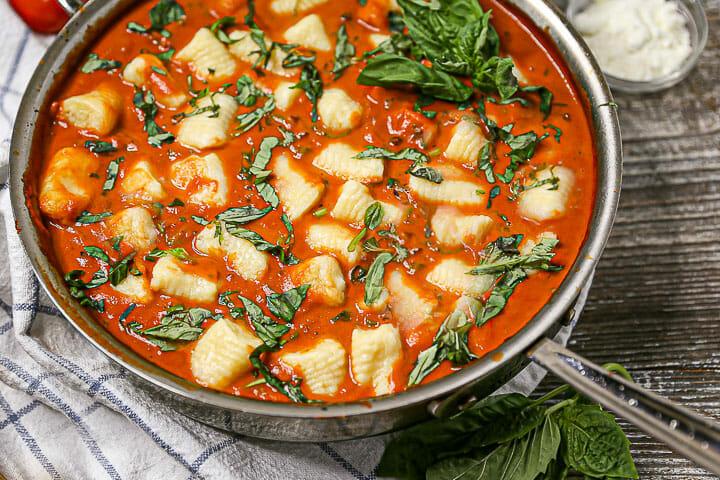Gnocchi in Creamy Tomato Basil Sauce in a saucepan garnished with basil.