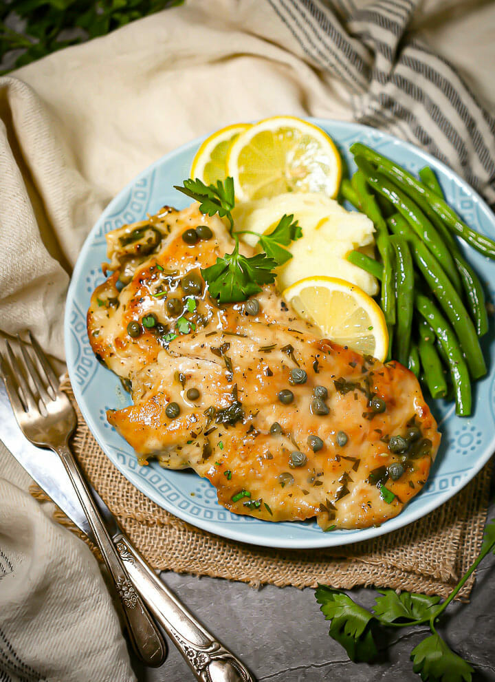 A serving of chicken piccata with green beans and mashed potatoes on a round blue plate with lemons.