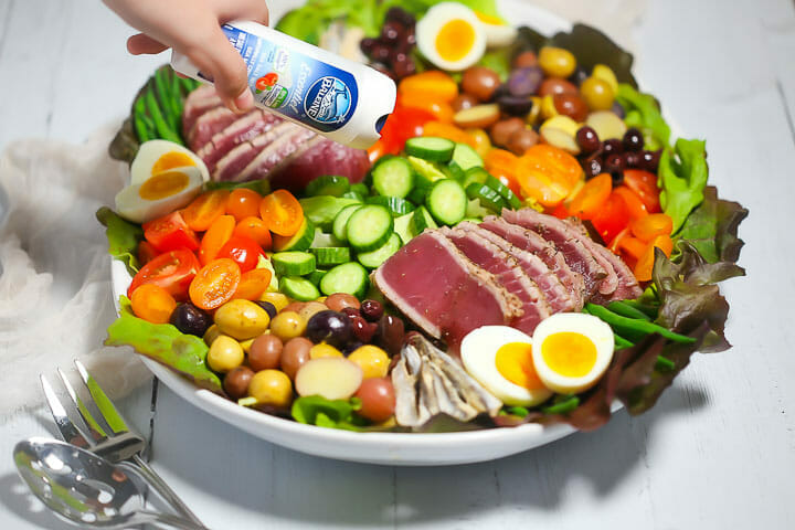 Sprinkling salt from a salt shaker onto a Seared Tuna Nicoise Salad.