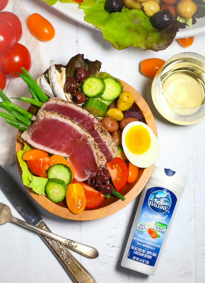 A serving of Seared Tuna Nicoise Salad with a slat shaker next to it.