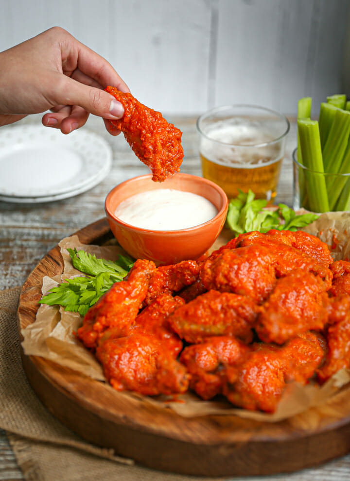 A hand dunking a baked buffalo wing into blue cheese.