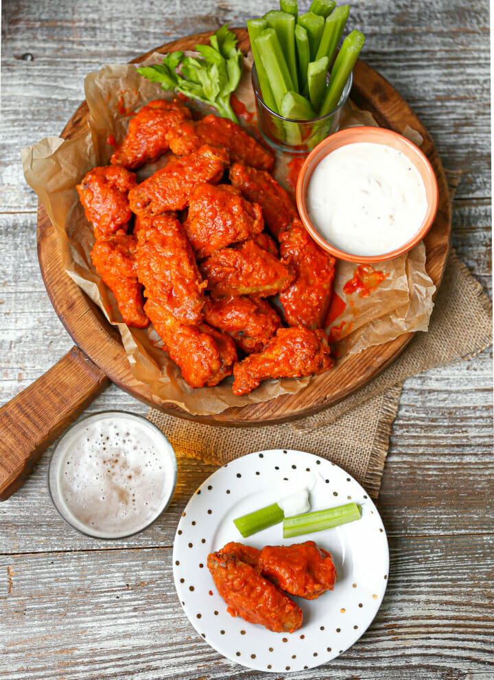Baked Buffalo wings on a round wood serving board with celery and blue cheese and serving plate on the table too.