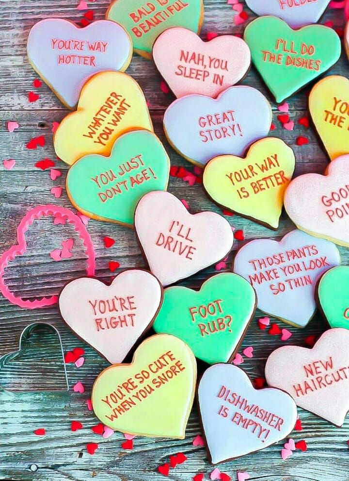 Vanilla and chocolate Conversation Heart Cookies inscribed with funny messages.
