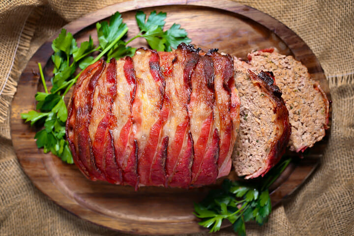 A bacon wrapped meatloaf on a tray with two slices cut.