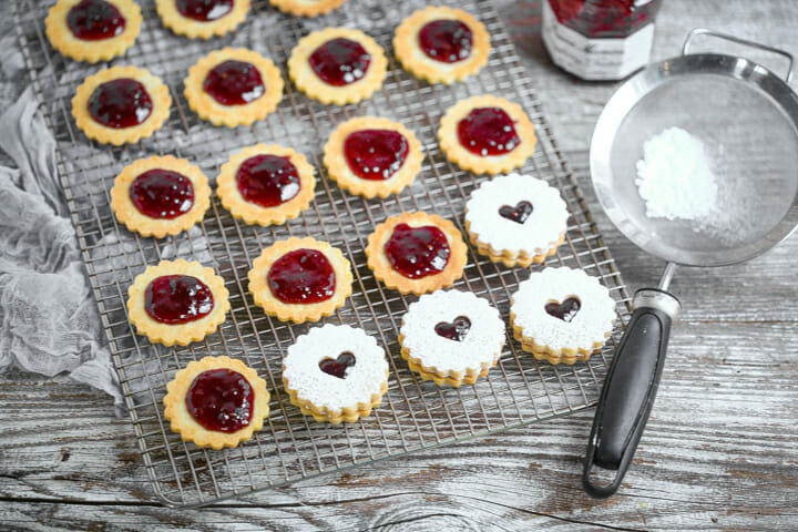 Linzer cookies being filled with raspberry jam and topped with a cut out cookie.