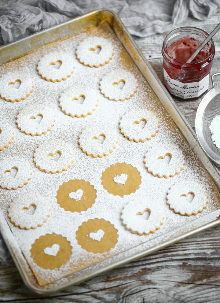 The top cookie of linzer cookies dusted with powdered sugar.