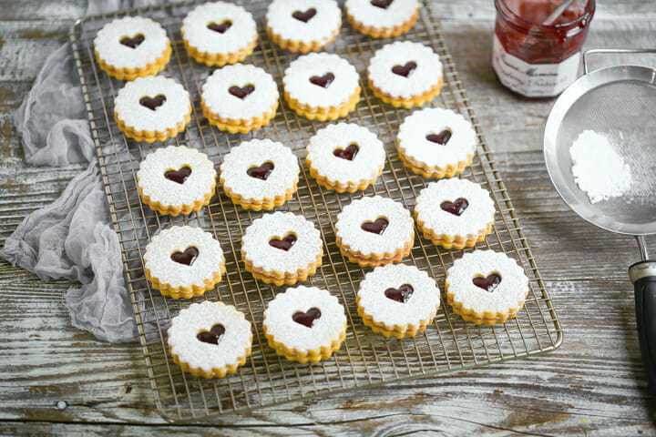 Linzer cookies on a bakers rack with a jar of jam and sifter with powdered sugar.