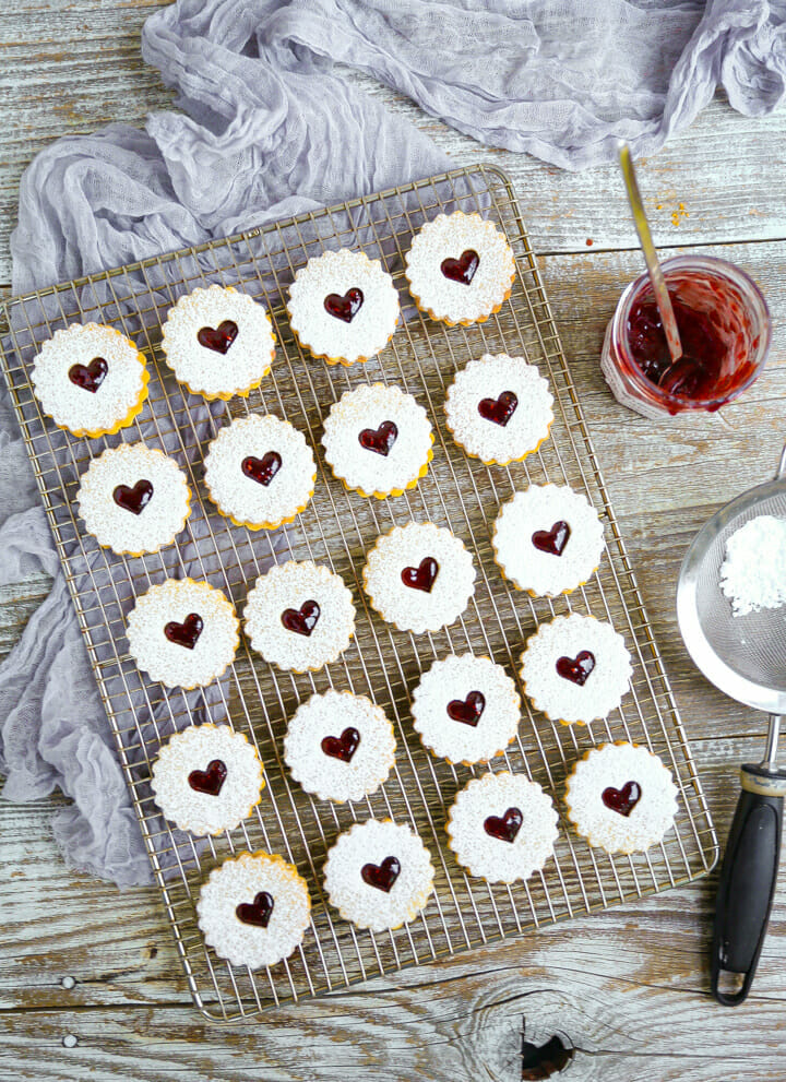 Overhead shot of nut-free linzer cookies on a bakers rack with a sifter with powdered sugar and a jar of raspberry jam.