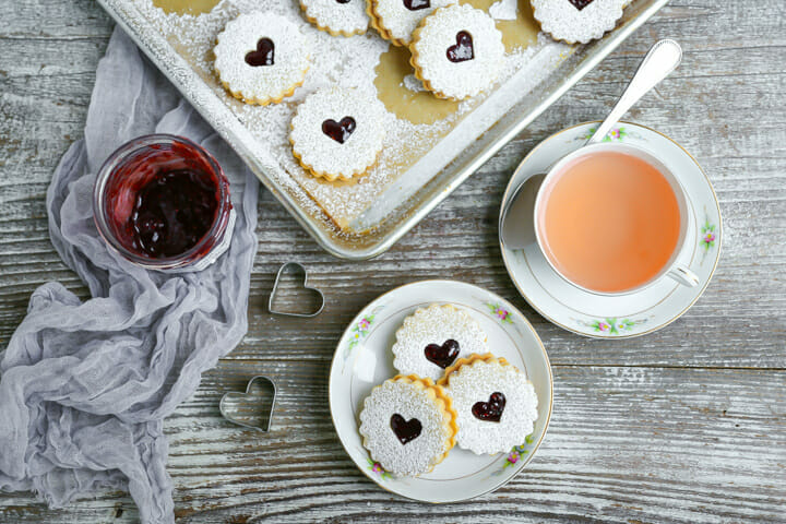 Nut-Free Linzer Cookies on a small dessert plateserved with a cup of hot tea and jam.