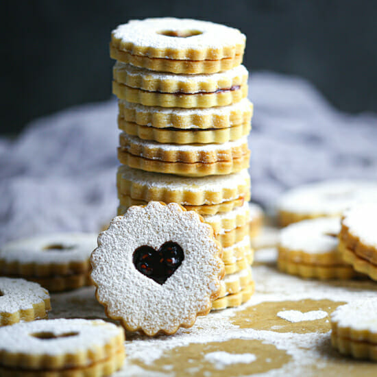 A stack of Nut-Free Linzer Cookies with one cookie with a heart shape cut out facing forward.