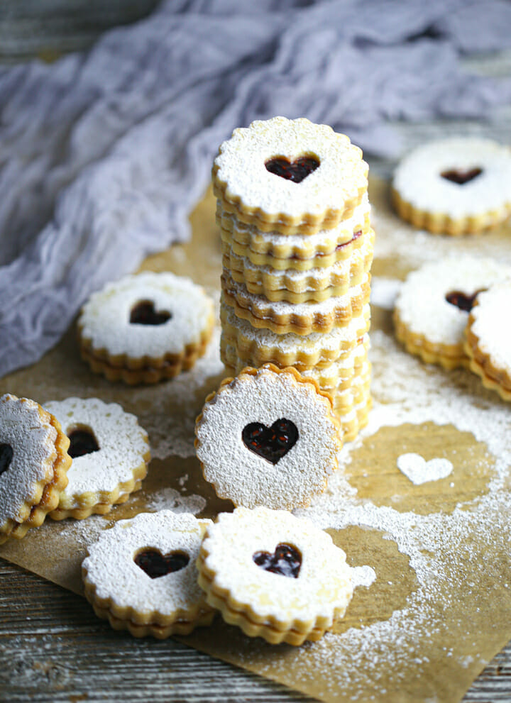 A stack of Nut-Free Linzer Cookies with other cookies scattered around.