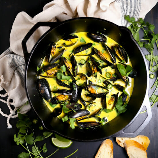 A pot of Curry Coconut Mussels with herbs and bread on scattered on the table.