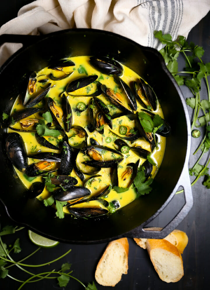 Curry Coconut Mussels in a large black pot with cilantro and chiles scattered over them.