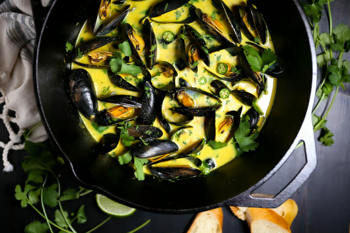 Close up of Curry Coconut Mussels sprinkled with cilantro.