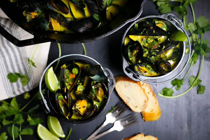 Two servings of Curry Coconut Mussels in small black crocks.